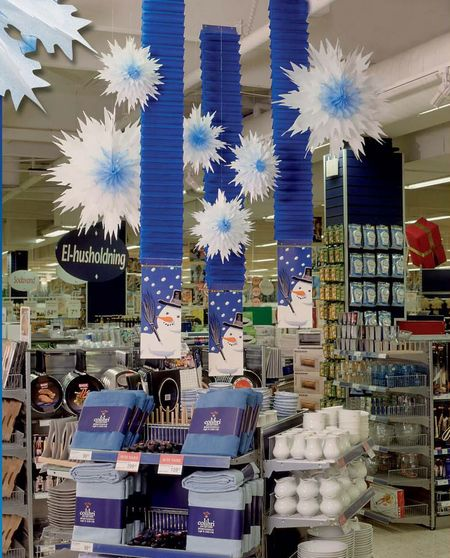 déco hiver - décoratioin d'un linéaire en GMS avec des kakemonos en accordéon et de grandes rosaces blanches en forme de cristaux de neige en papier gaufré