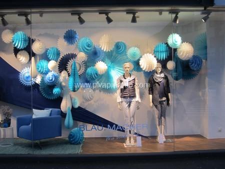 décoration de noël - vitrine de magasin décorée avec des boules et des rosaces en papier crépon bleu